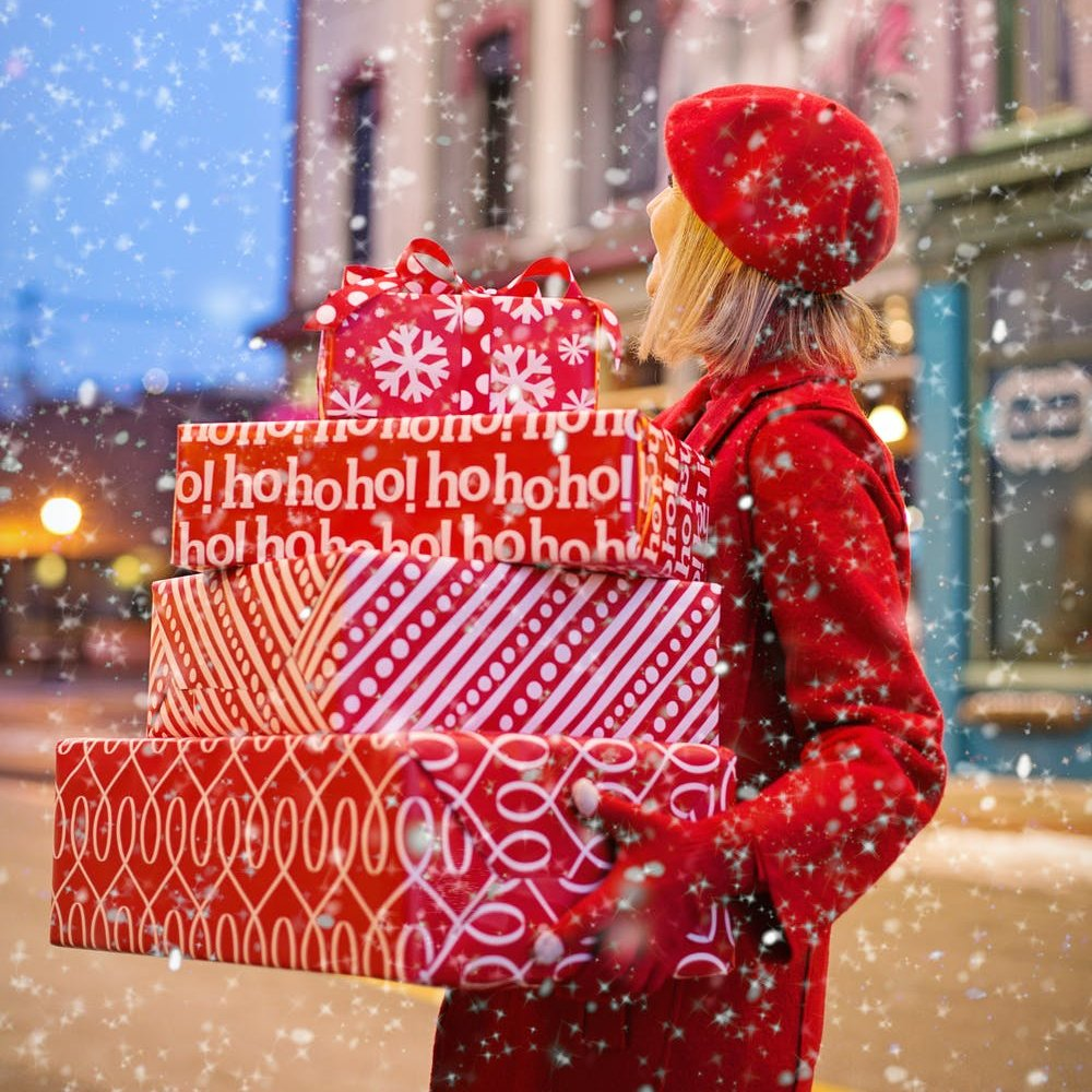 photo of happy woman holding many Christmas gifts
